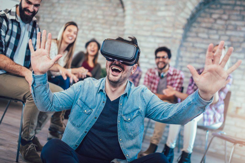 Junger Mann, der eine VR-Brill trägt und gerade gut gelaunt ein Training absolviert. Im Hintergrund ist eine Gruppe zu sehen
